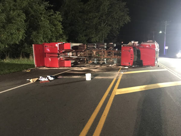 driver hurt as dump truck bed catches wires overturns in
